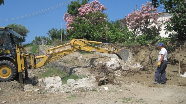 wall being cleared of remaining trees and dirt